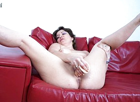 Naughty mature slut riding a dildo on her couch