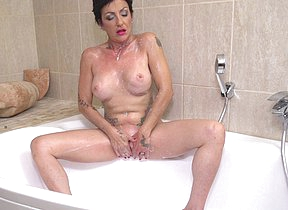 Horny housewife playing surrounding her shaved pussy in the bathtub