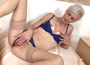 Naughty mature lady playing with her pussy on the couch