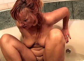 Old lady rubs her furry pussy in crazy modes while her saggy tits are shaking like crazy part of a sensual solo display in the tub to offer her Facetious Adams ale orgasms
